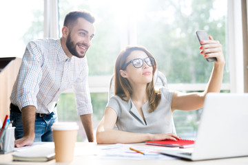Portrait of beautiful businesswoman wearing glasses taking selfie  with handsome colleague while sitting at desk in office  against window in sunlight