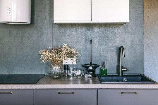 New stylish bright scandinavian interior details. Dark grey kitchen room organization. Pure water and clear sink