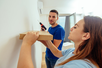 Attractive young couple installing a shelf on a wall using a power drill. Home decoration and renovation concept.