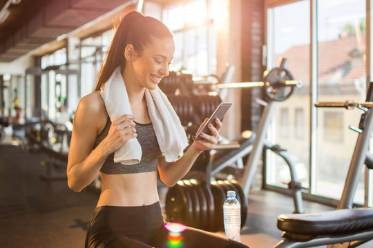 Young fit woman using smart phone at gym
