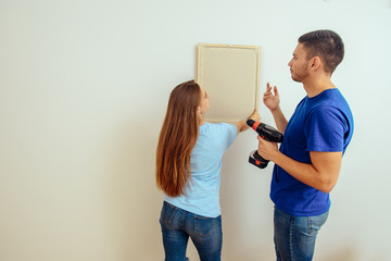 Married couple choosing place for picture in frame on the wall at home interior. Home decoration and renovation concept.