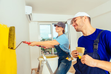 Portrait Of Young Couple Who Paint Walls With Paint Roller. Home decoration and renovation concept.