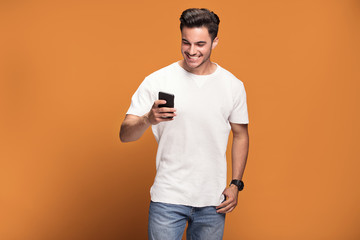 Smiling handsome man with mobile phone on yellow background.