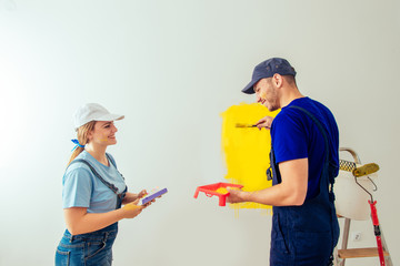 Smiling Couple In Overall Painting Room Together