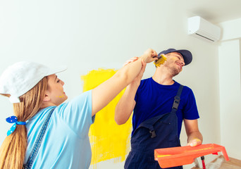 Romantic Couple Holding Paintbrush Together And Having Fun With Her Boyfriend painting each other. Home renovation concept.