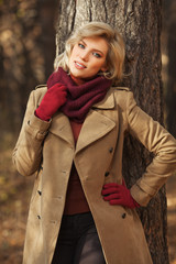 Young blond fashion woman in classic beige coat walking outdoor