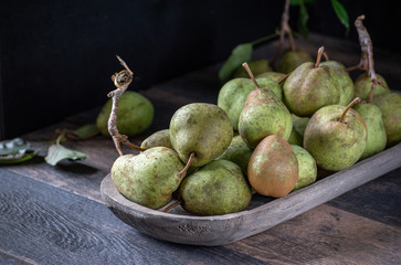 group of rustic pears with stems and leaves on rustic farm table