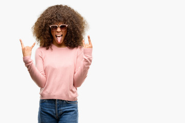 African american woman wearing pink sunglasses shouting with crazy expression doing rock symbol with hands up. Music star. Heavy concept.