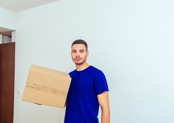 Handsome man holding cardboard box with items. Young family moving in concept.