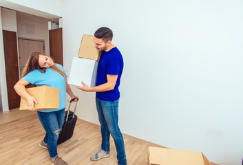 Happy Family Couple And A Lot Of Cardboard Boxes. Young family moving in concept.