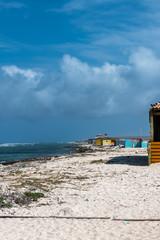 Aruba - Beach huts on windward coast under dramatic skies
