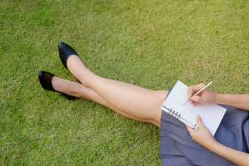 Working woman hands with pen writing on notebook on grass outside.