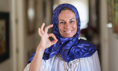 Middle age brunette arabian woman wearing colorful hijab doing ok sign with fingers, excellent symbol