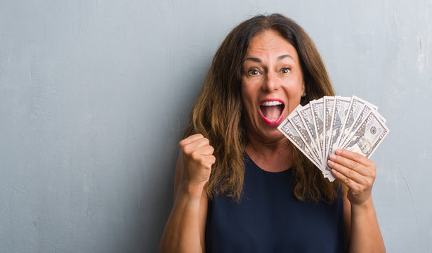 Middle age hispanic woman standing over grey grunge wall holding dollars screaming proud and celebrating victory and success very excited, cheering emotion