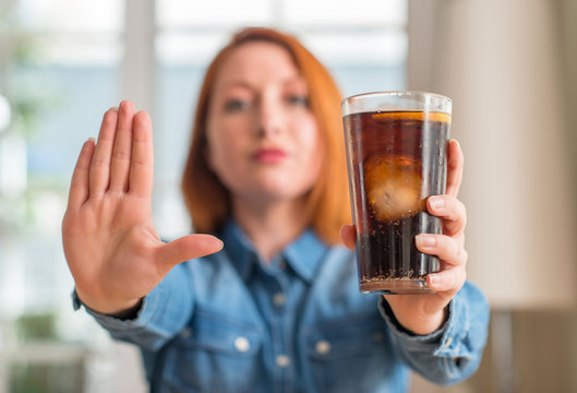 Redhead woman holding soda refreshment with open hand doing stop sign with serious and confident expression, defense gesture