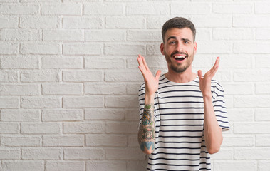 Young adult man standing over white brick wall very happy and excited, winner expression celebrating victory screaming with big smile and raised hands