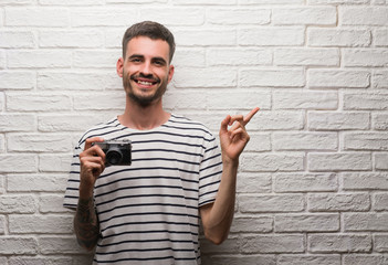 Young man holding vintage camera standing over white brick wall very happy pointing with hand and finger to the side