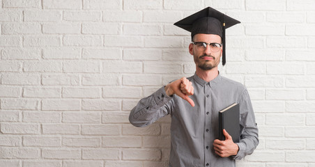 Young adult man over brick wall wearing graduation cap with angry face, negative sign showing dislike with thumbs down, rejection concept