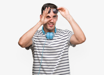 Handsome young man wearing headphones doing ok gesture with hand smiling, eye looking through fingers with happy face.