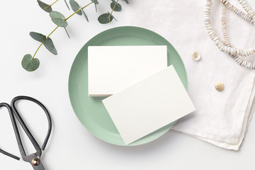 Minimalist feminine branding / business card mockup with stack of cards in a small bowl, scissors, boho necklace and eucalyptus twigs on a styled desk. Mint, white and neutral hues. Flat lay.