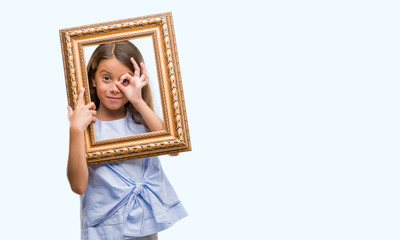 Brunette hispanic girl holding vintage art frame with happy face smiling doing ok sign with hand on eye looking through fingers