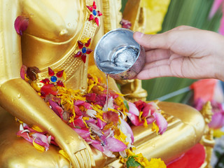 Close up hand watering to golden buddha statue