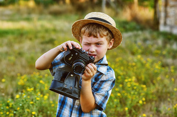 A boy with an old camera in the open air .The concept of learning photography
