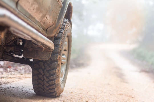 Wheel closeup in a countryside landscape with a muddy road, Off-road travel on mountain road,Adventure Travel, Rainy Season.