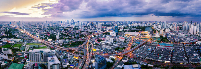 Wall Mural - Aerial view of Bangkok skyline and skyscraper with light trails on express way in center of business in Bangkok downtown. Panorama of Bangkok smart city in Thailand at sunset.