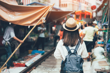 Young asian woman traveler visiting in Maeklong railway market is the most famous traditional traditional market unseen in Thailand at Maeklong district in Samut Songkhram near Bangkok Thailand