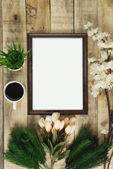 Wood picture frame and coffee with flower decoration on wood background. Rustic nostalgia flat lay.