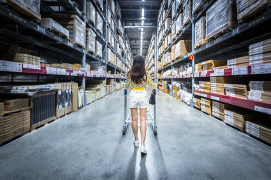 Young asian woman pushing shopping cart in warehouse shopping / blurred warehouse background material.