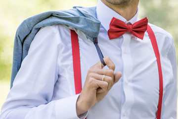 The groom in a white shirt with a bow tie and in suspenders holds a jacket