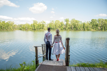 The beautiful bride and groom stand on the pier by the river, hold hands in summer