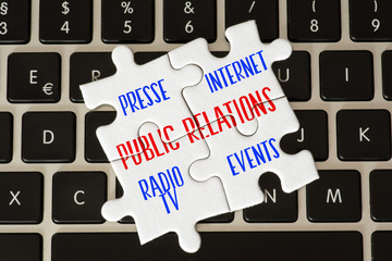 Ein Computer, ein Puzzle und verschiedene Teile von Public Relations