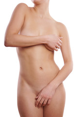 naked female body of unrecognizable young woman covering breasts and pubic area with her hands