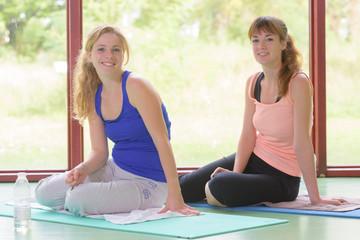 Two ladies sat on yoga mats
