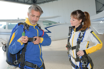 Man and woman preparing for parachute jump