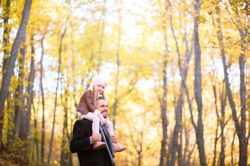 Autumn fashion for children and the whole family. A small daughter sits on the shoulders of the father in the neck against the background of the yellow autumn forest.
