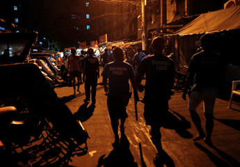 Policemen and Barangay watchmen patrol as they look for teenagers lingering in the streets in Tondo, Manila