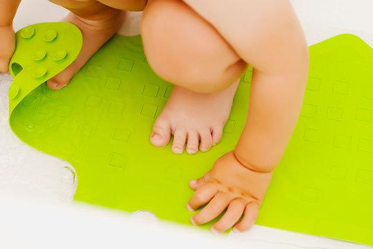 Baby feet in bathtub on anti slip rubber mat for bathroom