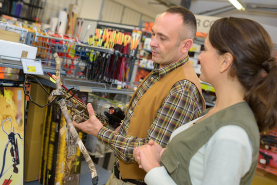 Man in shop looking at crossbow