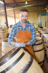 wood barrels production cooper using hammer and tools in workshop