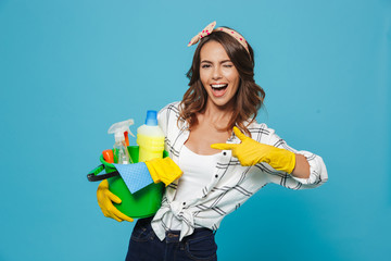 Photo of pleased young housemaid 20s wearing yellow rubber gloves for hands protection holding bucket with cleaning supplies, isolated over blue background