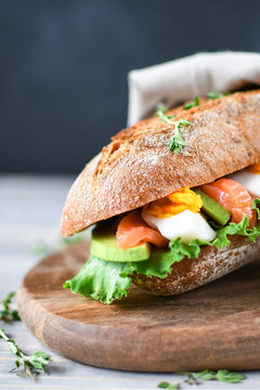 French lunch: sandwich from a cereal baguette with avocado, salmon, egg and lettuce leaves and Camembert cheese,