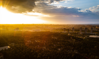 Aerial drone view of residential area with huge city forest, capital of South Ural in sunny evening after rain, park of culture and recreation on the foreground, Russia