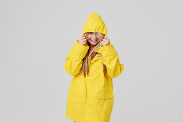 Woman in a yellow raincoat on a gray background