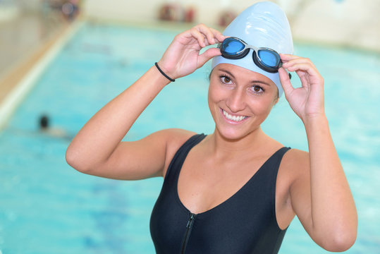 Portrait of female swimmer wearing goggles and hat