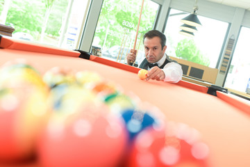 man positioning cueball to break at pool game