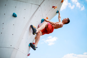 Photo from bottom of strong athletic man exercising on wall for climbing against blue sky with clouds